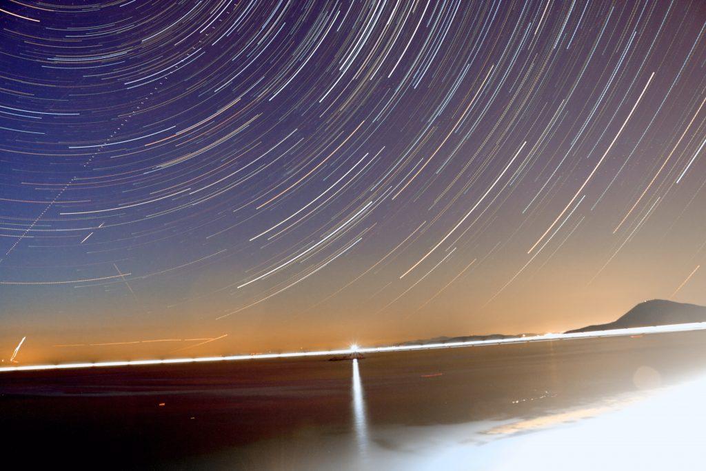 Visione suggestiva della spiaggia Le ghiaie. Sono presenti il faro dello Scoglio, l'Italia, aerei in decollo da Pisa, una meteora, scie varie di aerei e satelliti.